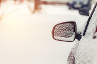 The car is all covered with snow. Snow on rearview mirror. Concept of driving in winter time with snow on road. Toned photo with copy space.