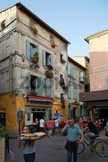 Arles, Frankreich. Junge Kellnerin trägt Pizza über die Straße