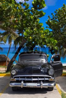 Amerikanischer schwarzer Oldtimer parkt am Strand in Varadero Cuba - Serie Cuba Reportage