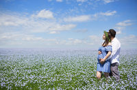 Happy beautiful pregnant couple in linen field