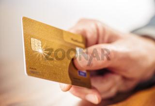 Hand mit goldener Kreditkarte