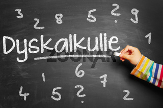 Kind schreibt Dyskalkulie an Tafel in Schule