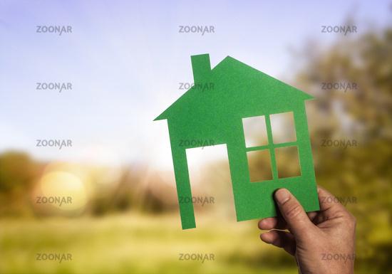 Scherenschnitt eines Hauses vor sonniger Landschaft