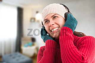 Woman wearing winter clothes listening music indoors