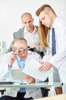 Älterer Mann als Klinik Chef mit seinem Ärzteteam