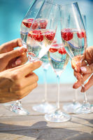 Hands with Champagne glasses with raspberry