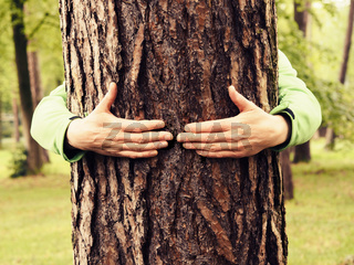 Young man hugs a tree