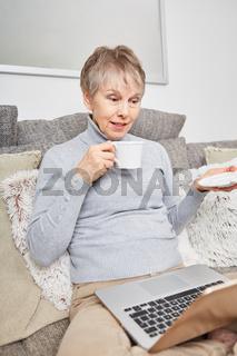 Seniorin chattet entspannt mit dem Laptop