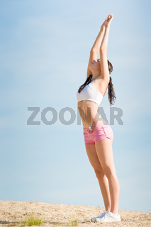 Summer sport fit woman stretching on beach