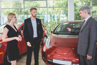 Vehicle manager showing electro car to young couple.