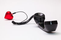 Old phone reciever and cord connection with red heart.