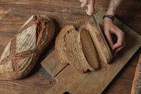 Women's hands cut organic bread