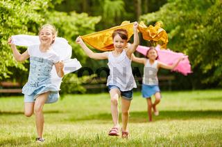 Kinder mit Tüchern im Wind fühlen sich frei