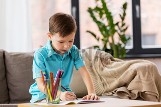 boy with notebook and pencils drawing at home