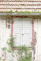 Fenster mit Fensterläden in einem verfallenen Haus
