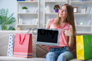 Young woman with shopping bags indoors home on sofa