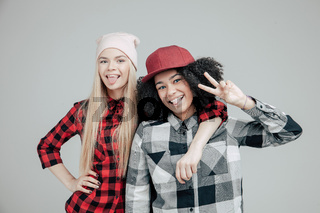 Studio lifestyle portrait of two best friends hipster girls going crazy and having great time together. Isolated on white background.
