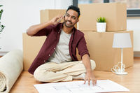 man moving to new home and calling on smartphone