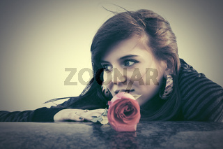Happy young woman with a red rose outdoor