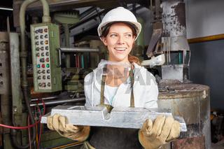 Frau trägt ein Stahl Werkstück in Gießerei