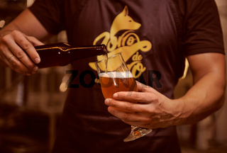 Man pouring beer to the glass