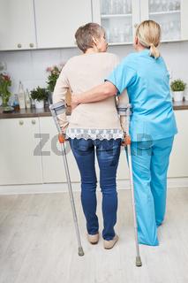 Behinderte Seniorin an Krücken lernt laufen