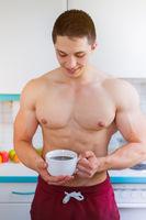 Kaffee trinken Bodybuilder junger Mann trinkt in der Küche Hochformat Morgen