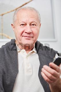Mann als Rentner mit einem Smartphone