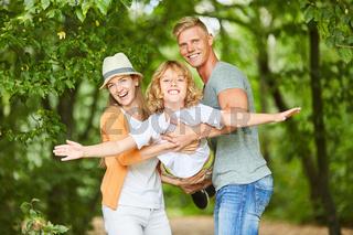 Vater und Mutter halten ihren glücklichen Sohn