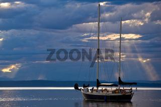 A sailboat on a calm sea at dusk