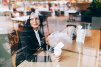 Successful business woman with smart phone sitting in a cafe