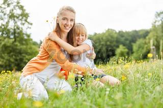 Mutter wird von Mädchen liebevoll umarmt