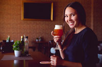 Young happy brunette drinking a beer in a restaurant