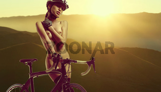 Naked woman with a bicycle. Desert at sunrise on a background.