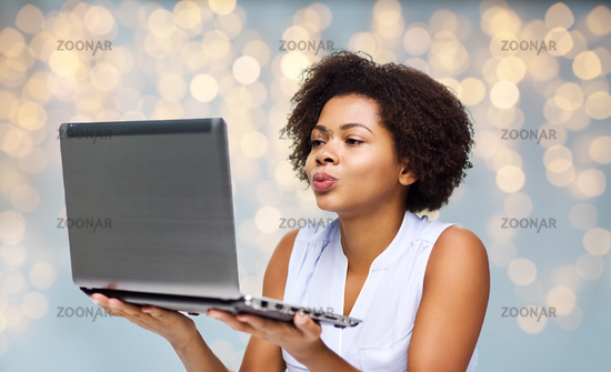 woman with laptop computer sending kiss to someone