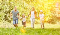 Familie und Kinder laufen im Sommer in Natur