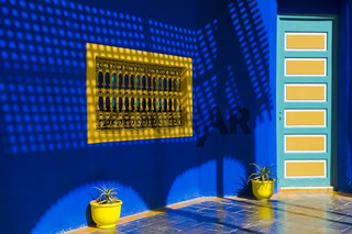 Yello Pots and Window in a Blue Wall