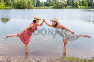 Two women standing together in natural water