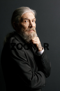 Old man with long grey hair and beard on black background.