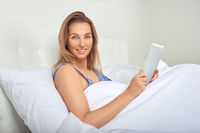 Attractive woman relaxing in bed with a tablet computer