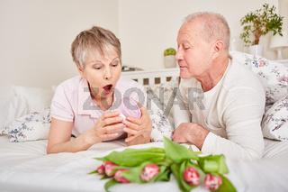 Seniorin schaut überrascht auf ein Geschenk