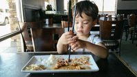 Cute Young Chinese and Caucasian Boy Learning To Use Chopsticks At Restaurant