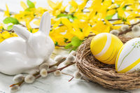 An easter nest with yellow easter eggs on a rustic background