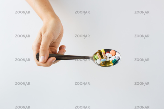 close up of female hand holding spoon with pills