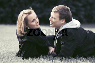 Happy young couple in love lying on the grass outdoor