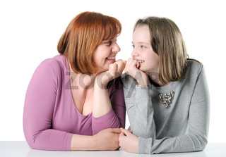 Woman and teen girl sitting together at a table and looking at each other.