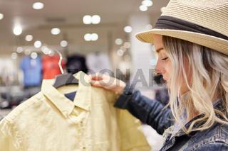 Mädchen bei Auswahl einer Bluse im Laden