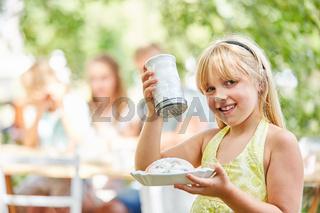 Mädchen mit Zuckerstreuer und Kuchen