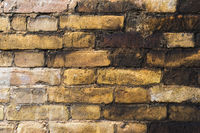 Textured background of old faded bricks stained with black oil. A brick gradient between dirty black and light yellow bricks. Grunge style