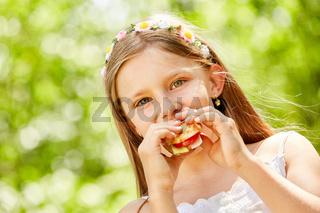 Mädchen mit Blumen im Haar isst ein Baguette